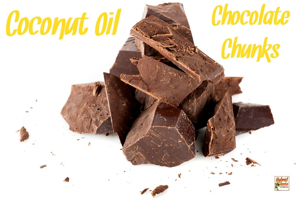 Coconut oil chocolate chunks in a pile on a white background