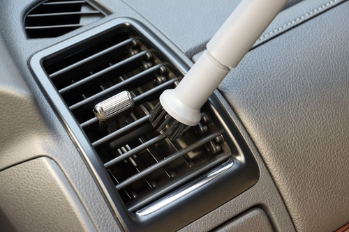 A car detailing brush going across a car air vent with tan interior.