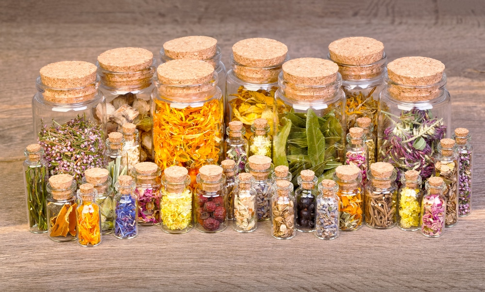 Healing herbs in bottles for herbal medicine on old wooden table - herbal remedies for children
