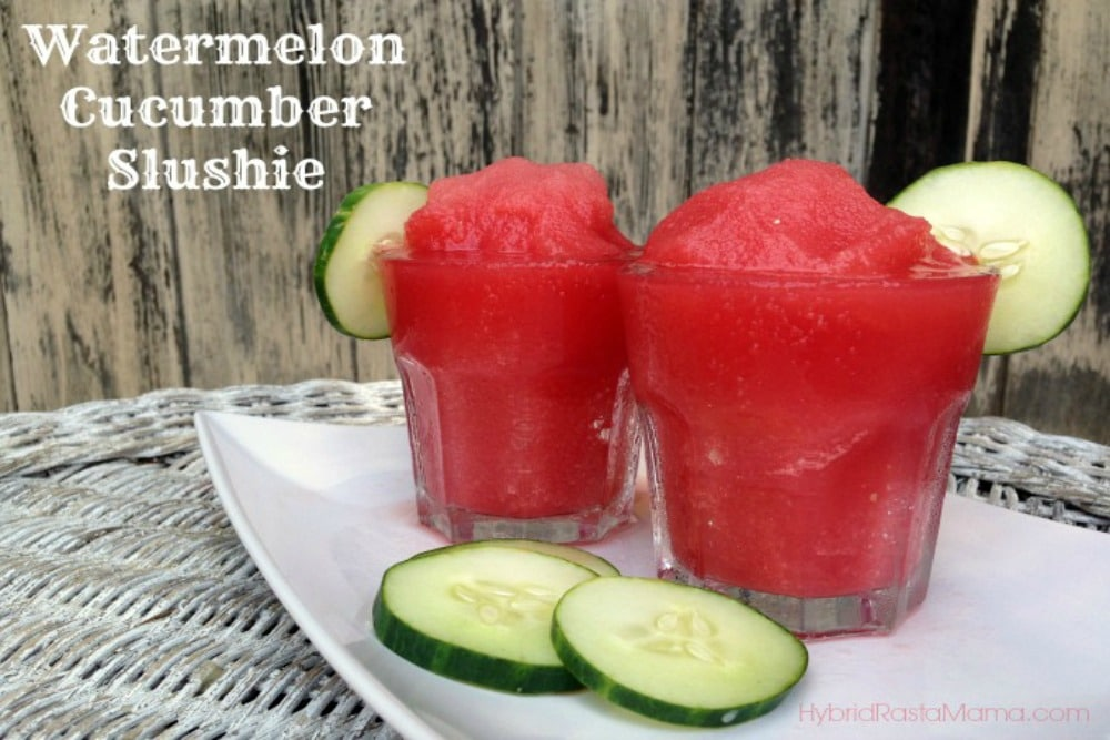 Two glass jars of watermelon cucumber slushies with a cucumber slice on the rim